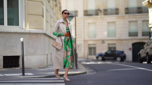 gabriella berdugo wears sunglasses, a green floral printe silky midi skirt co ord with blouse , a long leather with mid sleeve beige jacket, mesh... - sleeve stock videos & royalty-free footage