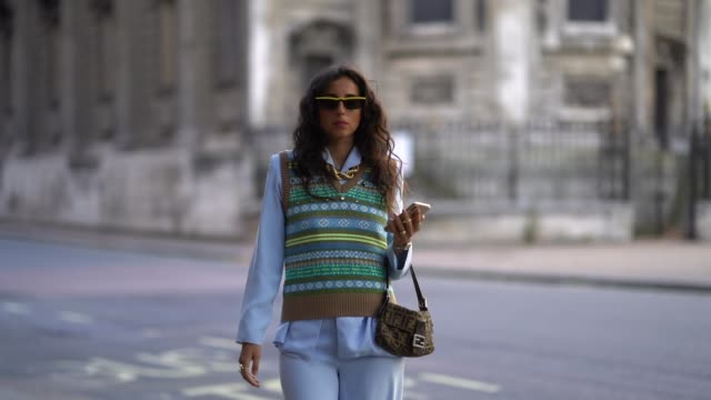 gabriella berdugo wears sunglasses, a pale blue jacket, flare pants, yellow shoes, an off shoulder wool top with printed colored patterns, a fendi... - handheld stock videos & royalty-free footage