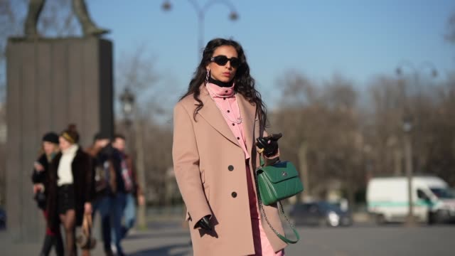 stockvideo's en b-roll-footage met gabriella berdugo wears sunglasses a salmon color oversized blazer jacket a green quilted chanel bag pink cropped pants golden shiny high boots black... - zwart jak