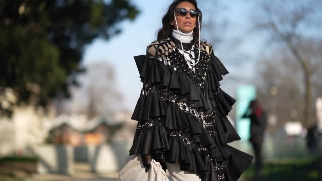 stockvideo's en b-roll-footage met gabriella berdugo wears sunglasses a turtleneck pullover a black ruffled oversized dress with large mesh black leather gloves a white puff bag white... - coltrui