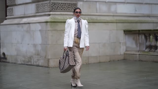 gabriella berdugo wears sunglasses, a white jacket with shoulder pads, a shirt, a blue tie with white polka dots, quilted pants, white boots, a gucci... - spotted stock videos & royalty-free footage