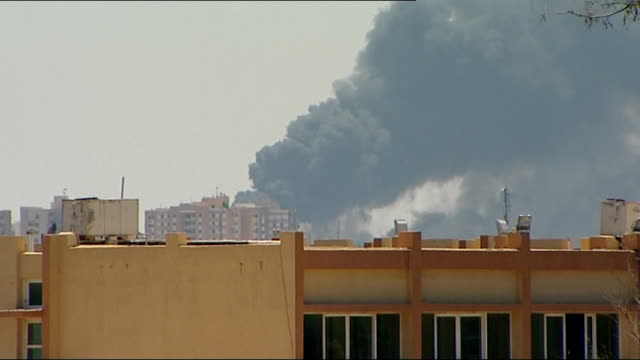 vídeos de stock, filmes e b-roll de gaddafi defiant amidst increased nato bombardment; libya: tripoli: ext view over city as explosion from nato attack heard and a column of flame and... - air raid