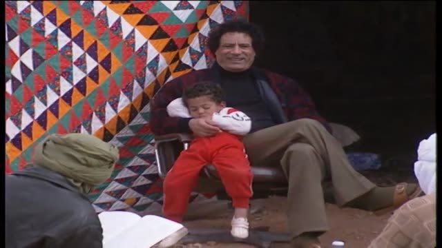 gaddafi sits outside his tent, cuddling with a small boy. - home movie video stock e b–roll