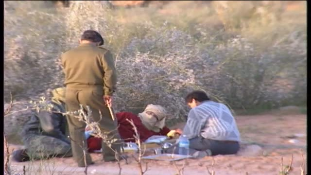 gaddafi with members of his entourage sitting next to a dirt road by a small fire / men get ready to cook freshly skinned bird carcasses on a... - land rover stock videos & royalty-free footage