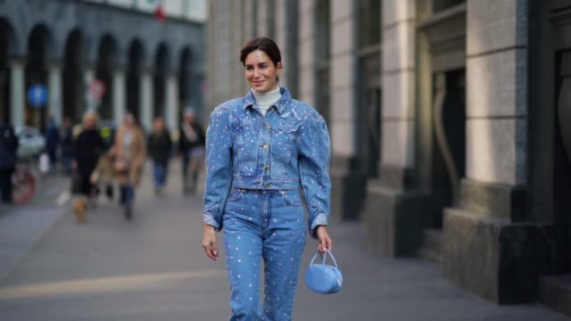 gala gonzalez wears a blue denim jacket with shoulder pads, a white turtleneck pullover, blue denim pants, cowboy boots, a bag, outside philosophy,... - milan fashion week stock videos & royalty-free footage