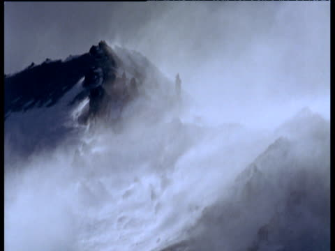 Gales blow snow over misty mountain peaks