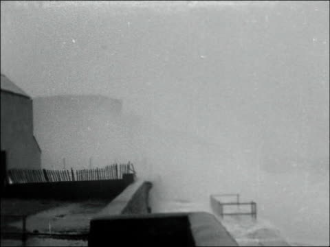 folkestone ext car along stormy sea front / large waves brekaing against and over sea wall / woman struggling with umbrella in gale force winds / tx... - gale stock videos and b-roll footage