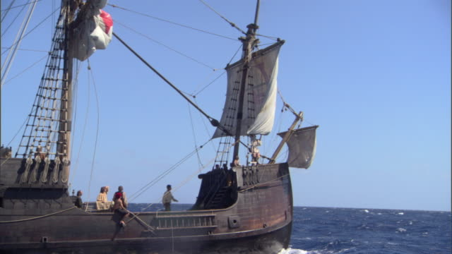 a galleon cruises over the ocean as deckhands work. - seeräuber stock-videos und b-roll-filmmaterial