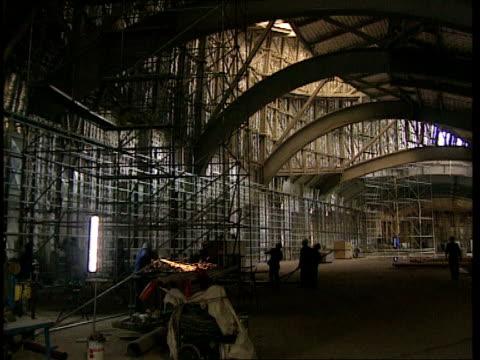 vidéos et rushes de bilbao: guggenheim museum; sequence construction work going on inside new museum, featuring welder at work on steel framework and internal views of... - museum