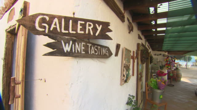 zi gallery and wine tasting signs on building wall beneath porch with green overhang / baja mexico - fels stock-videos und b-roll-filmmaterial