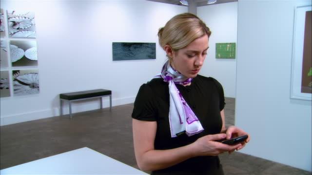 vídeos y material grabado en eventos de stock de gallery owner text messaging on smartphone / folding arms and looking at art offscreen / looking at camera - museo de arte