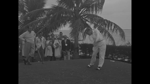 gallery walks across course at bahamas country club in nassau / group shot golfers with the duke of windsor, now governor-general of the bahamas, and... - エドワード8世点の映像素材/bロール