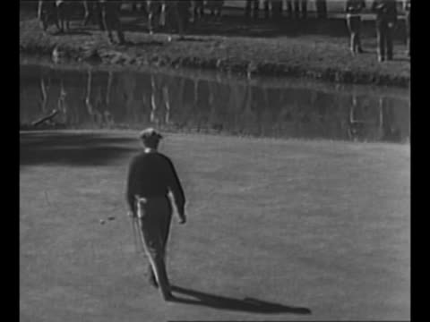 Gallery walks away from camera at 1950 Los Angeles Open / Hogan putts / rear shot uniformed African American spectator in gallery / Hogan sinks small...