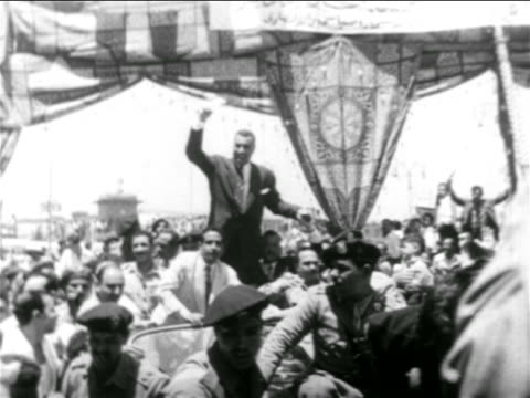 vídeos de stock e filmes b-roll de gamal abdel nasser standing up in car waving in middle of crowd outdoors / egypt - 1956