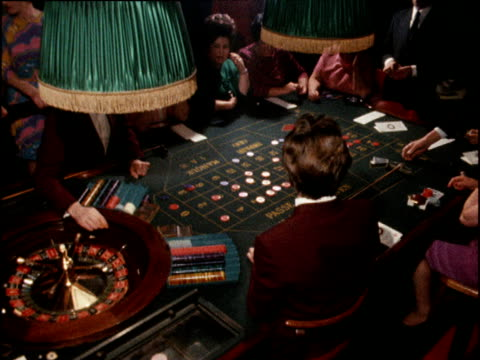 gamblers gathered around roulette wheel following the gaming act; 07 nov 68 - roulette stock videos and b-roll footage