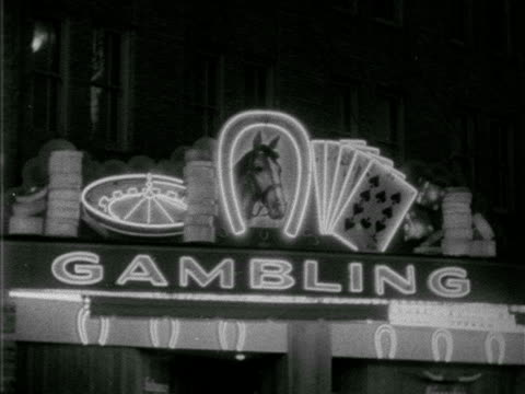 ws 'gambling' along top roof edge w/ roulette wheel flashing upside down horseshoe framing horse head five playing cards fanned out w/ light outline... - horseshoe stock videos and b-roll footage