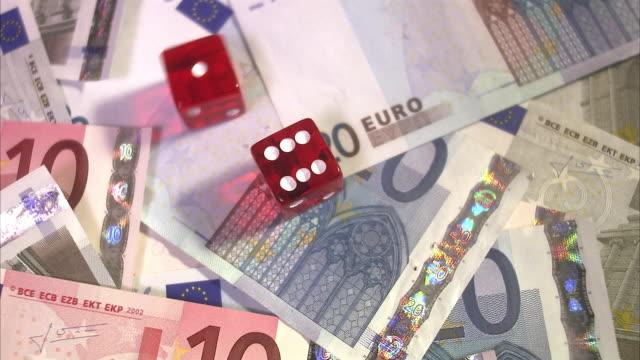 stockvideo's en b-roll-footage met a game of dice on a pile of euro bills. - tien euro