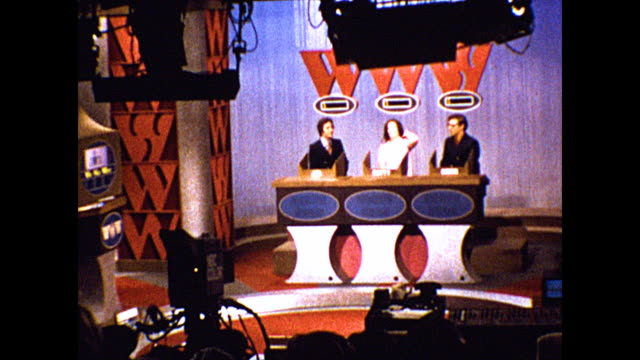 "game show contestants and employees prepare to shoot an episode of ""the who, what, or where game."" footage taken from studio audience vantage point. - gioco televisivo video stock e b–roll"