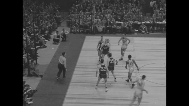 vs game with notable players for holy cross in light uniforms #22 togo palazzi #24 tom heinsohn #21 joe early #12 walt supronowicz and for duquesne... - tom green stock-videos und b-roll-filmmaterial