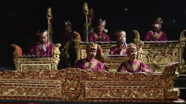 vídeos de stock e filmes b-roll de ms gamelan musicians are playing traditional balinese gamelan orchestra in puri saraswati temple audio / ubud, bali, indonesia, asia - gamelão