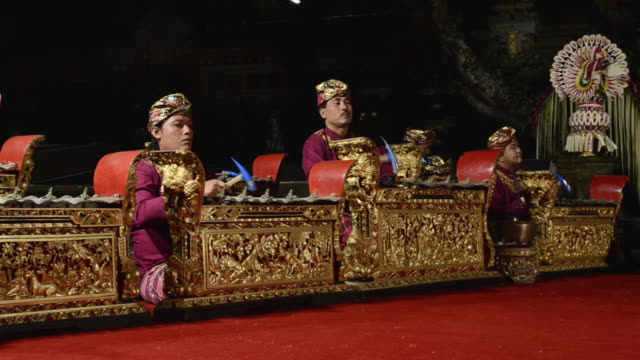 vídeos de stock e filmes b-roll de ms pan gamelan musicians are playing traditional balinese gamelan orchestra in puri saraswati temple audio  / ubud, bali, indonesia, asia - gamelão
