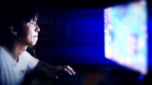 自宅で彼のパソコンでオンラインビデオゲームをプレイゲーマー - 30代点の映像素材/bロール