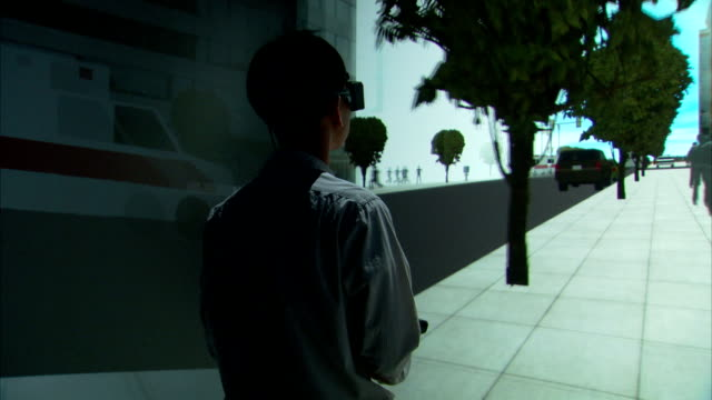 A gamer wearing virtual reality glasses appears to walk through a video game on a big screen.