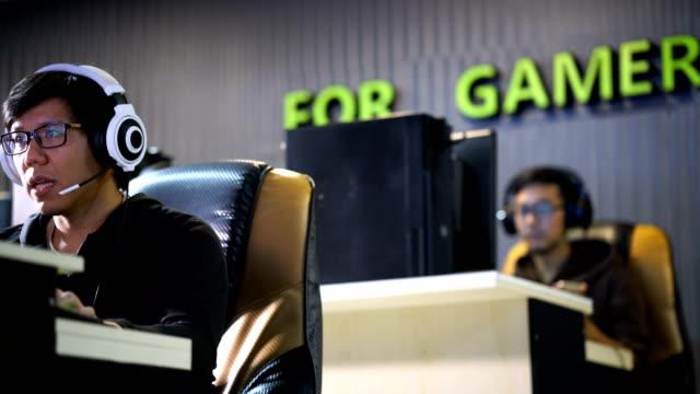 Gamers playing computer video game wearing headset