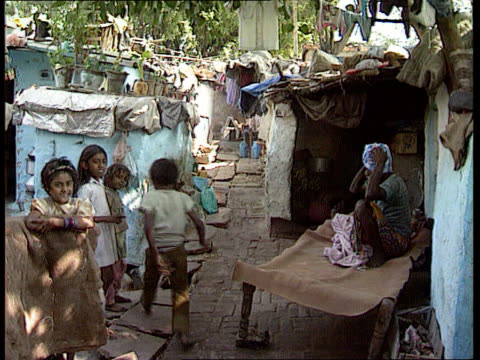 Gandhi assasination aftermath / wife nominated ITN LIB SEQ Street scenes TMS Children standing around amidst poor housing CMS Woman wringing out...