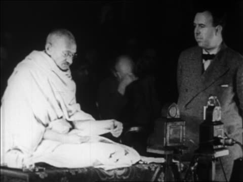 vidéos et rushes de gandhi sitting on platform as man speaks next to him / geneva switzerland / newsreel - 1931
