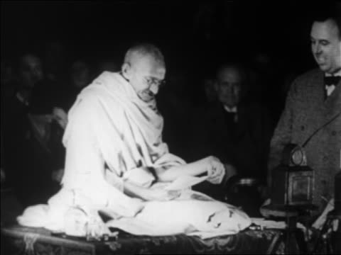 vidéos et rushes de gandhi sitting on platform speaking as man stands by him / geneva switzerland / newsreel - 1931