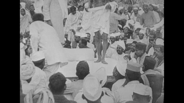 stockvideo's en b-roll-footage met gandhi takes a seat on the ground, sitting on a white sheet / side view he sits on an outdoor platform during a gathering of his followers / crowd on... - mahatma gandhi