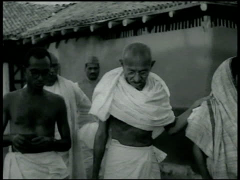 stockvideo's en b-roll-footage met gandhi's ashram . mohatma [mohandas karamchand] gandhi w/ outside others ext gandhi walking talking w/ male wiping back of hand w/ cloth while... - mahatma gandhi