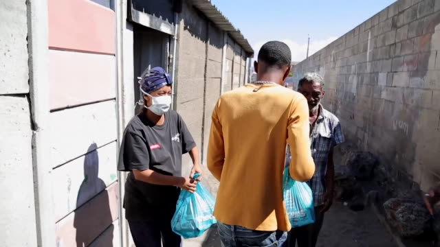 gang members in cape town have called a ceasefire to turf wars and are using their drug delivery networks to now deliver food to poor households due... - チンピラ点の映像素材/bロール