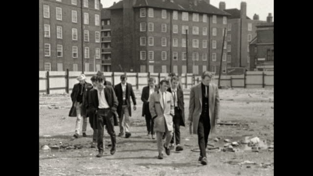 gang of teddy boys walk over derelict ground; 1969 - 30 seconds or greater stock videos & royalty-free footage