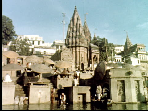 vidéos et rushes de 1960 montage ganges river. temples. boat glides past varanasi ghats. people washing clothes and meditating in river / varanasi, india - 1960
