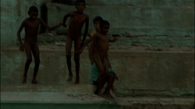 vídeos de stock, filmes e b-roll de gangotri glacier and varanasi waterfront naked young boys jumping into river - nu