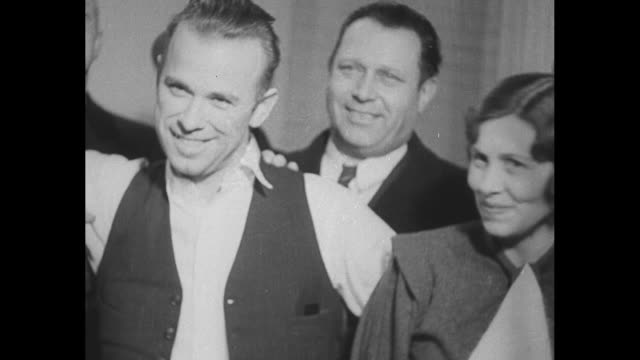 gangster john dillinger in custody in crown point in poses with sheriff lillian holley lake county prosecutor robert estill stands behind cu... - john dillinger stock-videos und b-roll-filmmaterial