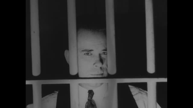 gangster john dillinger stands behind bars in jail cell while in custody in tucson az / note exact day not known film has nitrate deterioration - john dillinger stock-videos und b-roll-filmmaterial