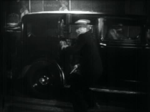 B/W 1934 gangster opening car door turns to shoot gun but gets shot himself