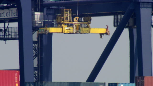 MS PAN TD TU Gantry crane grabbing containerand hoisting  from containership seen through heathaze / felixstowe, Suffolk, United Kingdom