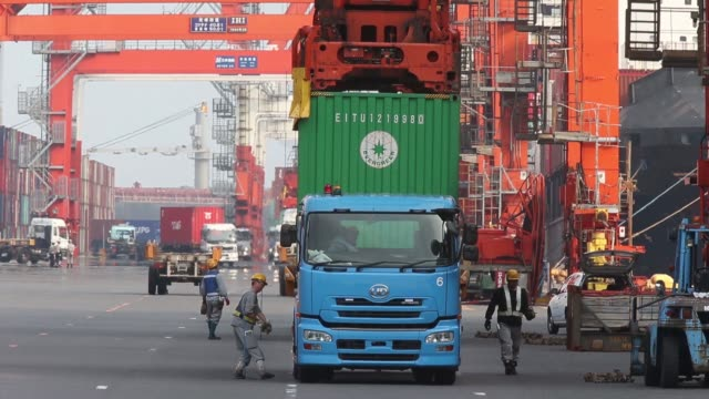 A gantry crane lifts a container from a moored ship at a shipping terminal in Tokyo Japan on Wednesday Aug 10 Gantry cranes load containers onto...