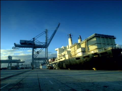 stockvideo's en b-roll-footage met gantry crane lowers boom towards docked cargo ship in harbour, south africa - laten zakken