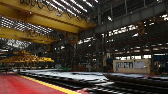 A gantry crane moves a sheet of steel at the Hyundai Mipo Dockyard Co shipyard an affiliate of Hyundai Heavy Industries Co in Ulsan South Korea on...