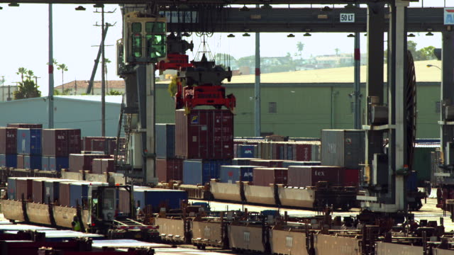 MS Gantry crane moving shipping container from freight rail car and drops container onto truck bed / San Pedro, California, United States