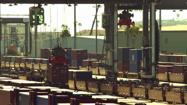 MS T/L  Gantry crane picking up shipping containers from rail cars and dropping them on to container hauling fleet trucks / San Pedro, California, United States