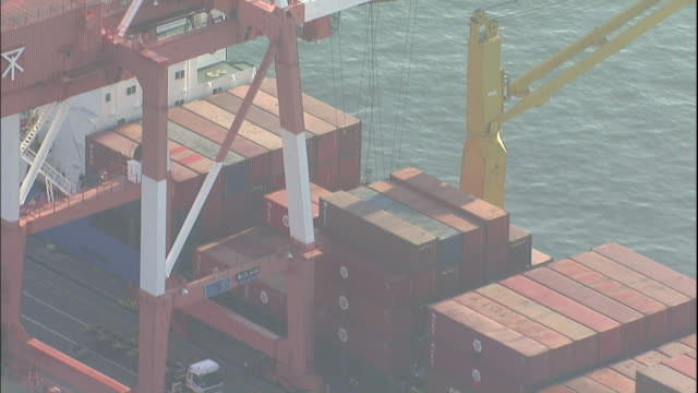 a gantry crane transports a container from a ship onto a truck in the osaka south port in japan. - straddle carrier stock videos & royalty-free footage