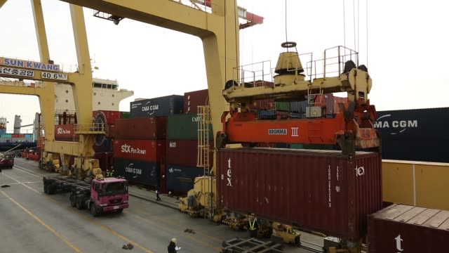 stockvideo's en b-roll-footage met gantry cranes load freight containers onto trucks at the sun kwang incheon container terminal in incheon south korea truck drives towards and away... - incheon
