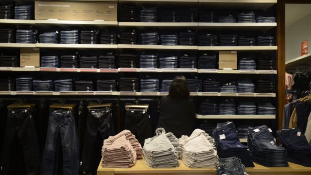 Gap Inc logo is displayed on denim pants at a Gap Inc Store in San Francisco California US A customer browses a row of jeans at a Gap in San...