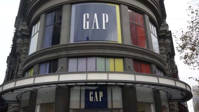 gap inc signage is seen on the facade of a gap inc store in san francisco california customers and shoppers walk into and out of a gap in san... - markenname stock-videos und b-roll-filmmaterial